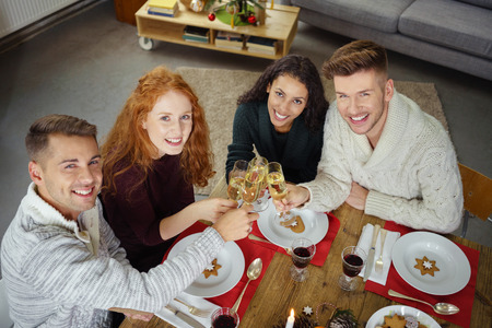 dinner party: group of friends toasting with champagne while having christmas dinner