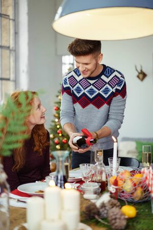 eating dinner: man pouring wine to his girlfriend´s glas while having christmas dinner
