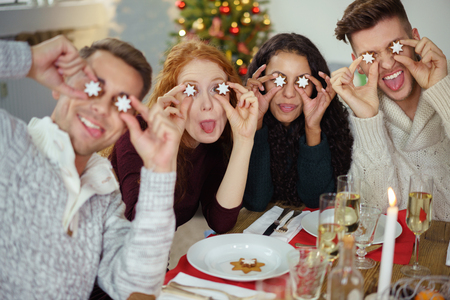 hilarity: friends putting christmas cookies on their eyes in the form of stars Stock Photo