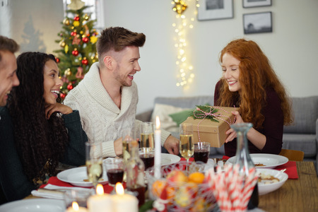 mirth: friends having christmas dinner and a man handing a christmas present to his girlfriend Stock Photo