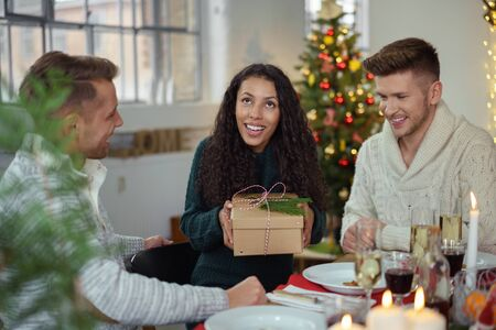 giftwrapped: friends having christmas dinner and a man handing a christmas present to his girlfriend Stock Photo