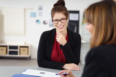 alkalmasság: Vonzó női jelentkezők egy állásinterjún ülés boldogan mosolyogva, mint a kérdező szól rajta keresztül önéletrajzát Stock fotó