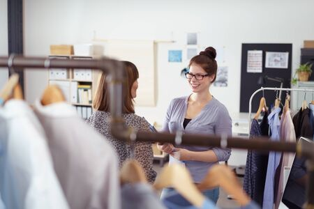 garments: Two businesswoman standing having a discussion surrounded by rails of garments in a fashion design studio