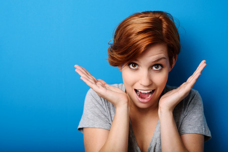 expression: Funny Woman Showing Surprise Facial Expression While Looking at the Camera Against Blue Wall Background.