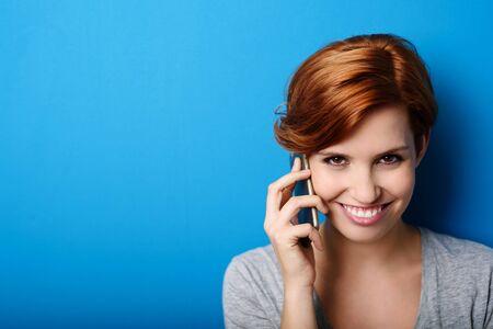 amigas conversando: Mujer Bonita llamar a alguien a través del teléfono móvil mientras sonriendo a la cámara contra el fondo de la pared azul con copia espacio.