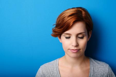 ojos cerrados: Cerca de fondo Pensativo joven mujer contra la pared azul con copia espacio en la izquierda. Foto de archivo
