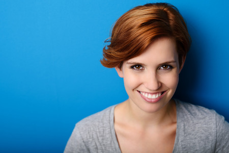 amiable: Head and Shoulder Shot of a Pretty Blond Woman Smiling at the Camera Against Blue Wall Background with Copy Space.