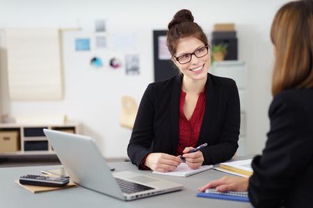 entrevista de trabajo: Empresaria dos en una reunión en la oficina, con especial atención a una atractiva mujer sonriente con gafas con una expresión atenta Foto de archivo