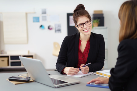Two businesswoman in a meeting in the office with focus to a smiling attractive woman in glasses with an attentive expression
