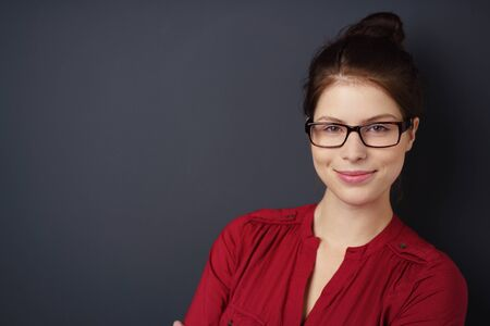 woman  glasses: beautiful young woman wearing glasses standing against black studio background Stock Photo