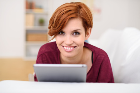 sincere girl: Portrait of an Attractive Young Woman Holding Tablet Computer While Relaxing at the Couch and Smiling at the Camera
