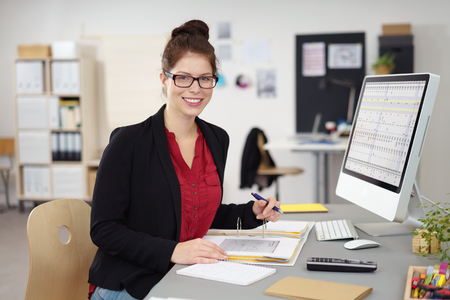 Smiling friendly businesswoman working in an office at her desk on some paperwork in front of the computer turning to smile at the camera Imagens