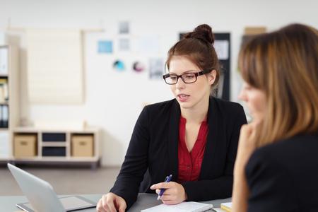 reunion de trabajo: Dos empresarias graves en una reunión sentados juntos en una mesa discutiendo la información en un ordenador portátil