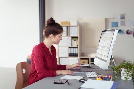 SECRETARIA: Elegante empresaria que trabaja en una computadora de escritorio sentado en el perfil de leer la informaci�n en la pantalla