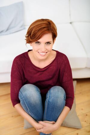 knees bent: Portrait of an Attractive Young Woman Sitting on the Pillow on the Floor and Smiling at the Camera. Stock Photo