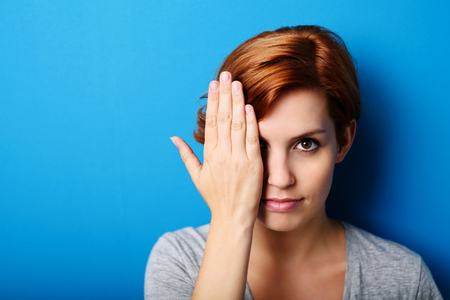 wall covering: Portrait of a Gorgeous Young Woman Covering Half Face with Hand and Looking at the Camera Fiercely Against Blue Wall with Copy Space.