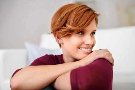 masaje facial: Cierre de la mujer bastante joven apoyando la barbilla en la mano y mirando a la derecha del marco con feliz expresión facial.