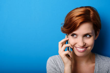 call: Close up Attractive Young Woman Listening to Someone Talking Through Phone Against Blue Wall Background with Copy Space. Stock Photo