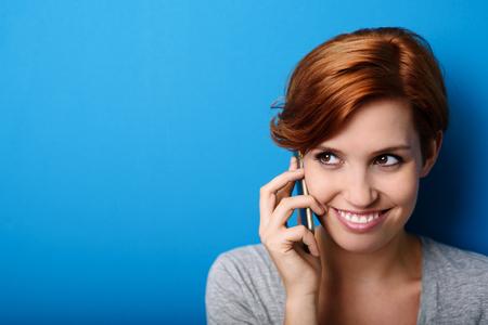 Zblízka Atraktivní mladá žena, poslech s někým mluví přes telefon proti modré zdi pozadí s kopií prostoru.