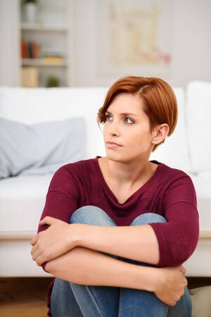 clasping: Pensive Young Woman Sitting on the Floor at Living Room and Looking Into the Distance. Stock Photo