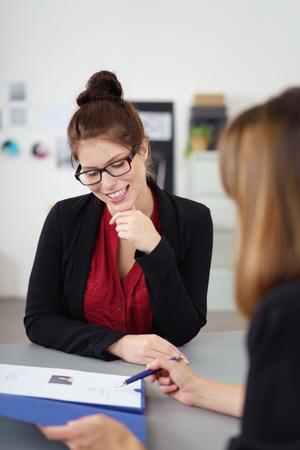 interview: Two businesswoman in a meeting sitting at a table discussing a document with a smile, possibly an employment interview