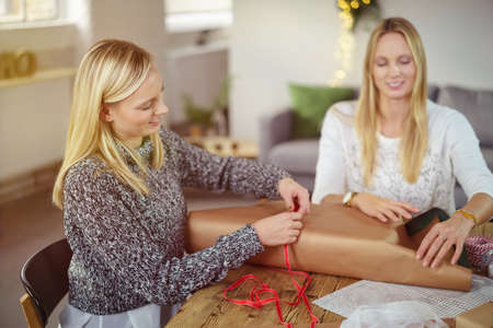 camaraderie: Two happy attractive young blond women sitting at a dining table at home gift wrapping presents for Christmas