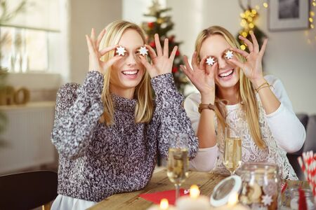 concealing: sisters putting christmas cookies on their eyes in the form of stars Stock Photo