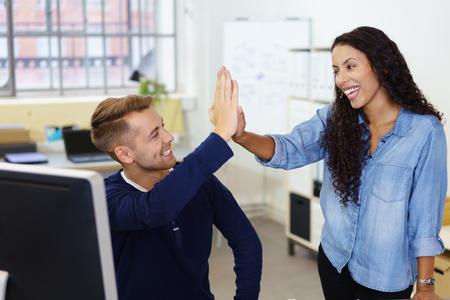 kolegové poskytující vysoký pět, protože slaví dobrý výsledek