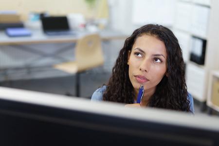 공중에 빤히 응시하는 사려 깊은 매력적인 사업가의 얼굴의 데스크톱 컴퓨터 모니터 상단에서 볼 수 있습니다. 스톡 콘텐츠