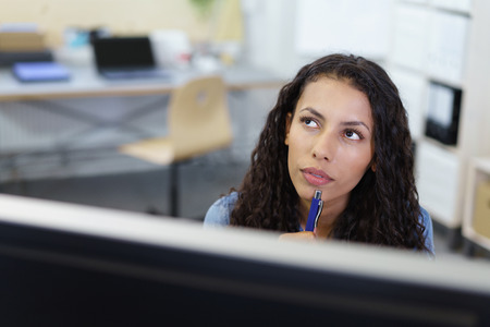 View over the top of a desktop computer monitor of the face of a thoughtful attractive businesswoman staring pensively into the air