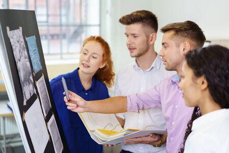 workteam: creative workteam standing at whiteboard discussing designs