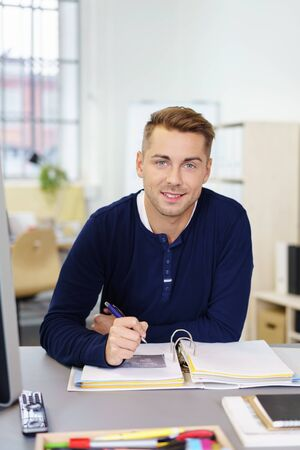 personal assistant: smiling young businessman sitting at a desk in the office writing notes Stock Photo