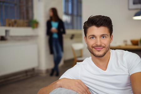 looking out: attractive man relaxing on the couch with a woman standing behind him looking out of the window