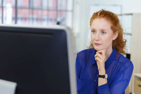 meticulous: Attractive young redhead businesswoman sitting at her desk in the office reading a desktop monitor with a serious expression Stock Photo
