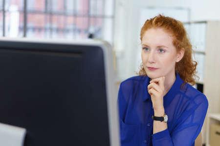 verlobt: Attraktive junge rothaarige Geschäftsfrau an ihrem Schreibtisch im Büro sitzt ein Desktop-Monitor mit einem seus Ausdruck lesen