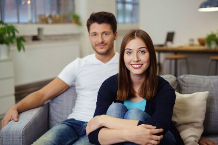 leans on hand: young man and woman sitting on the sofa with arms around her knees