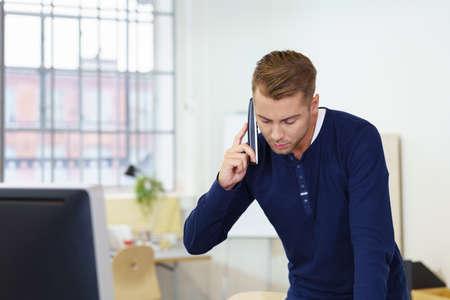 hablando por telefono: Joven hombre de negocios en el chat en su teléfono móvil como él se coloca apoyada en su escritorio n la oficina mirando hacia abajo mientras escucha Foto de archivo