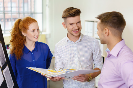 businesspeople: young businesspeople standing in the office talking
