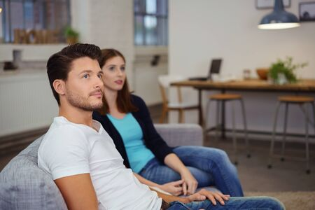 deadpan: thoughtful young couple sitting on their sofa at home in the evening