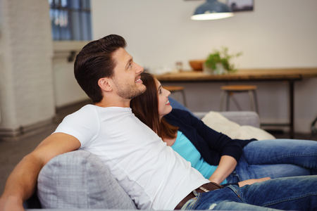 casual couple relaxing on the sofa with arms around each other looking up with a smile
