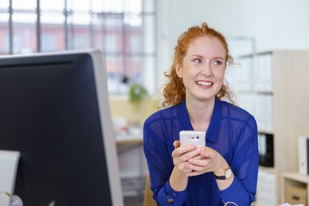 happy worker: Happy young office worker using a mobile phone for text messages looking to the side as she sits at her desk with a smile
