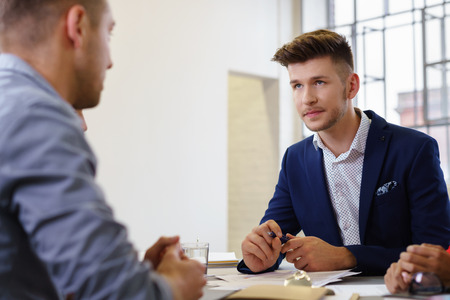 two men looking at each other in a business meeting