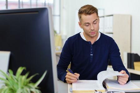 business report: casual young man reading documents at office