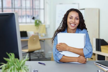 successful woman: successful woman sitting at the desk in the office holding a white binder Stock Photo