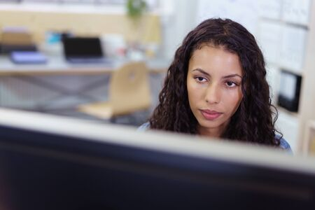 ethnic woman: overworked young businesswoman staring at computer monitor at the office Stock Photo