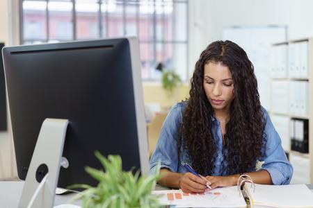 empleado de oficina: Jóvenes de negocios sentado en su escritorio en la oficina de análisis de un gráfico de barras con una expresión reflexiva seria