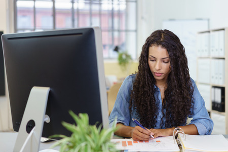 attractive office: Young businesswoman sitting at her desk in the office analysing a bar graph with a serious thoughtful expression Stock Photo
