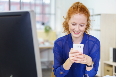 sitting at desk: Businesswoman sitting at her desk in the office reading a text message on her mobile phone with a smile of pleasure