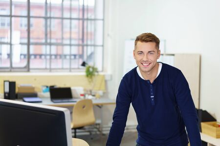 businessman in office: businessman standing at desk in the office looking at the camera with a smile Stock Photo