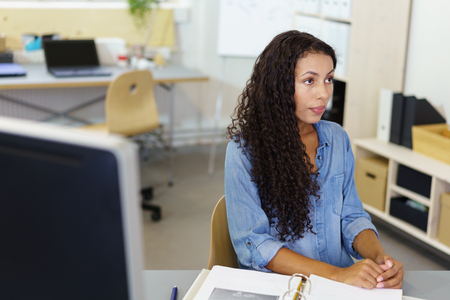 ethnic woman: serious businesswoman listening to someone a she is sitting at her desk in the office